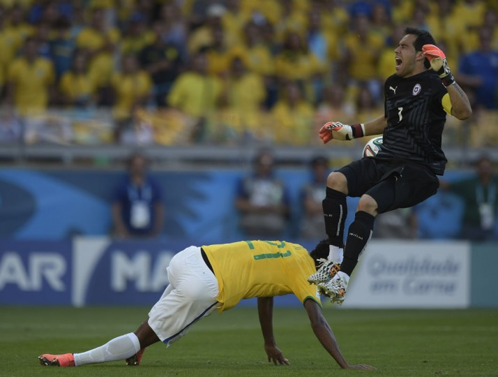 Chile's goalkeeper and captain Claudio Bravo (R) reacts after Brazil's forward Jo kicked him in the chest as he tried to score a goal during extra-time of the Round of 16 football match between Brazil and Chile at the Mineirao Stadium in Belo Horizonte during the 2014 FIFA World Cup on June 28, 2014. (Juan Mabromata/AFP/Getty Images)