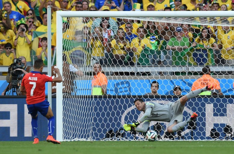 Brazil's goalkeeper Julio Cesar makes a save as Chile's forward Alexis Sanchez kicks the ball during the penalty shootout after the extra time in the round of 16 football match between Brazil and Chile at The Mineirao Stadium in Belo Horizonte during the 2014 FIFA World Cup on June 28, 2014. (Vanderlei Almeida/AFP/Getty Images)