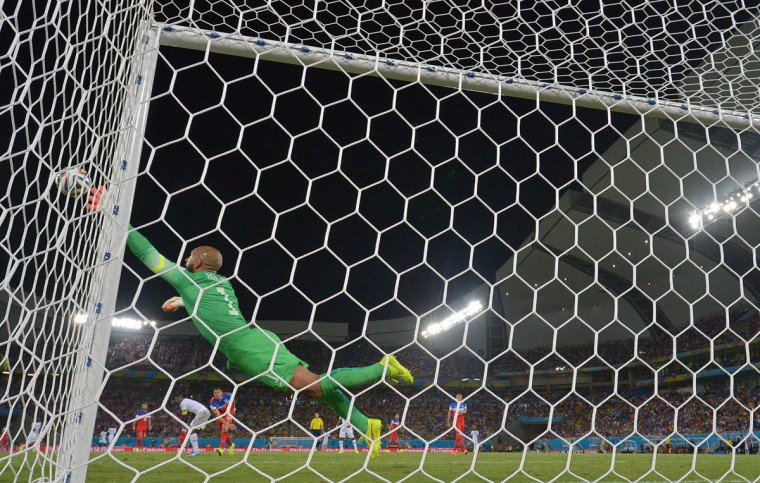 US goalkeeper Tim Howard dives for the ball during a Group G football match between Ghana and US at the Dunas Arena in Natal during the 2014 FIFA World Cup on June 16, 2014. (Carl De Souza/Getty Images)