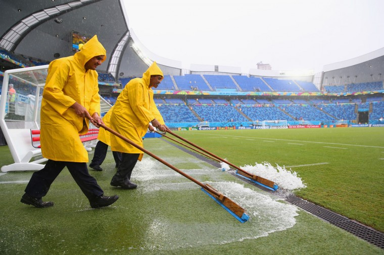 Stadium workers sweep rain water off the field toward a drain before the 2014 FIFA World Cup Brazil Group A match between Mexico and Cameroon at Estadio das Dunas on June 13, 2014 in Natal, Brazil. (Photo by Julian Finney/Getty Images)