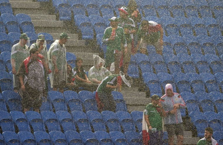 Mexican football fans wait for the start of a Group A football match between Mexico and Cameroon under pouring rain at the Dunas Arena in Natal during the 2014 FIFA World Cup on June 13, 2014. (Gabriel Bouys/AFP/Getty Images)