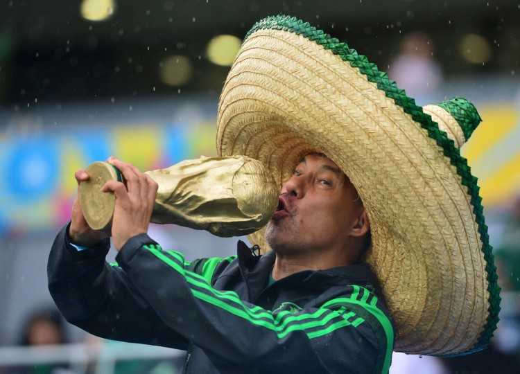 A Mexican football fan kisses a replica of the FIFA World Cup trophy before the start of a Group A football match between Mexico and Cameroon at the Dunas Arena in Natal during the 2014 FIFA World Cup on June 13, 2014. (Yuri Cortez/AFP/Getty Images)