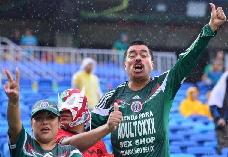 Mexican football fans cheer for their team as they wait for the start of a Group A football match between Mexico and Cameroon at the Dunas Arena in Natal during the 2014 FIFA World Cup on June 13, 2014. (Yuri Cortez/AFP/Getty Images)