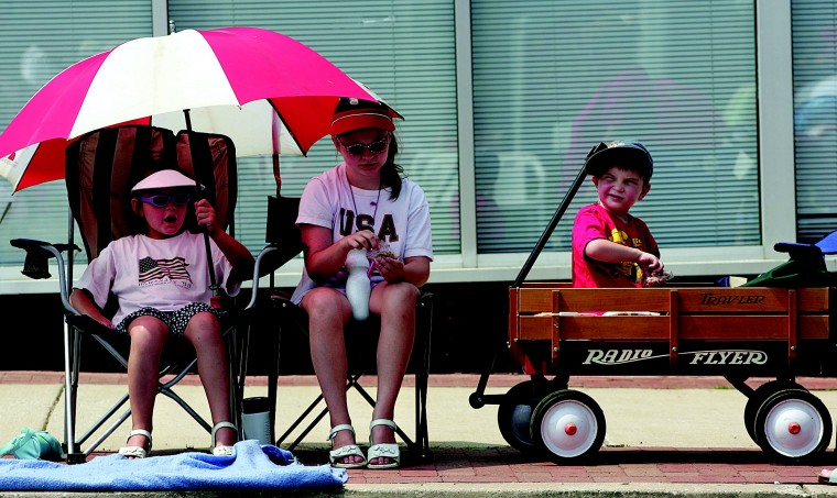 McKenzie McLain, 7, left, and her sister Mattison, 10, and brother McKennly, 4, wait for the Catonsville Independence Day parade to start on Monday, July 4, 2005. (Baltimore Sun Staff Photo by Hans Ericsson)