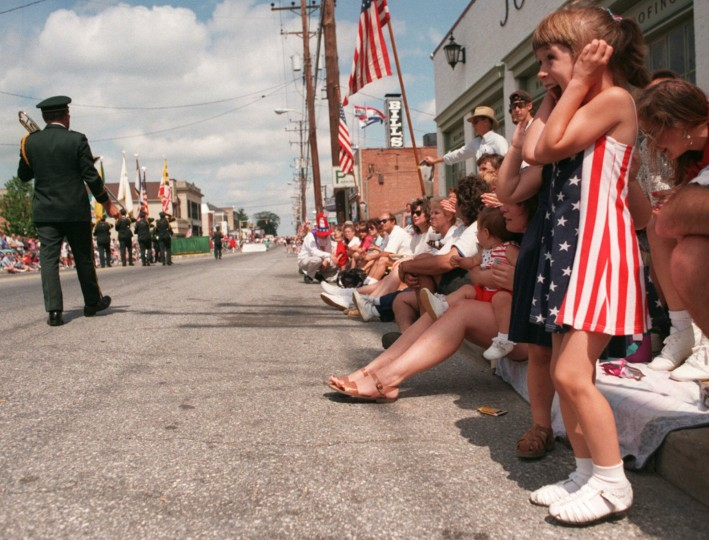 Samantha Iacia , 6, plugs her ears as a marching band goes by her at Catonsville's 50th Fourth of July Parade in 1996 on Frederick Road. (Baltimore Sun staff photo by Linda Coan)
