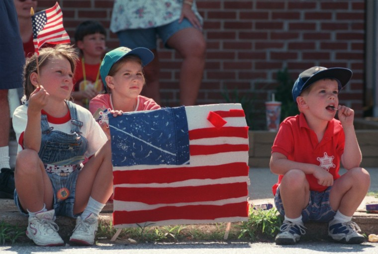 Kristin Mauerhan (cq) (left), Katie Heater and Andrew Heater of Catonsville hold up their hand made flag during the parade, July 4, 1997. (Baltimore Sun staff photo by Linda Coan)