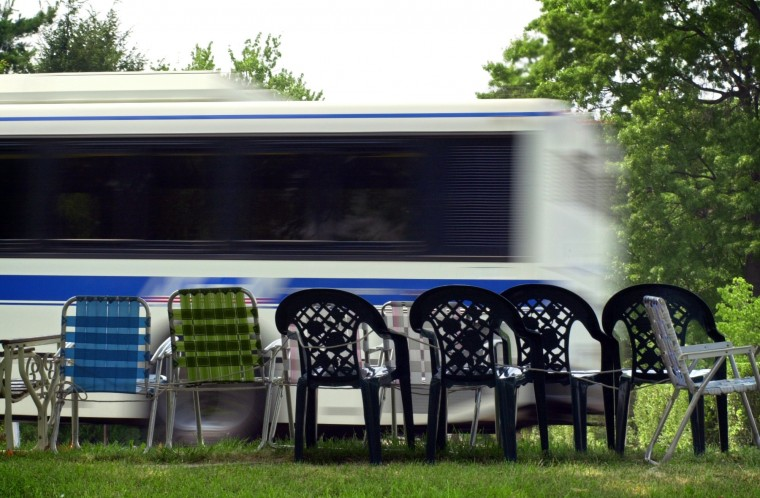 A public bus cruises west past a line of empty chairs, set there to reserve space on Frederick Av Mon., July 1, 2002 in preparation for the annual Independance Day Parade scheduled days later. Some residents say the placement of chairs is an annual tradition while others complain that holding space by using chairs and blankets has gotten out of hand. (Baltimore Sun/Karl Merton Ferron)