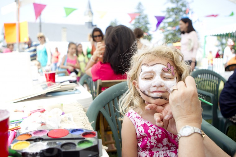 Volunteer Angie Gortayo of Clarksville paints Violet Smith's, 4, of Towson face to look like Hello Kitty during the 136th annual Clarksville Picnic at St. Louis Catholic Church in Clarksville, MD on Saturday, June 28, 2014. (Jen Rynda/BSMG)