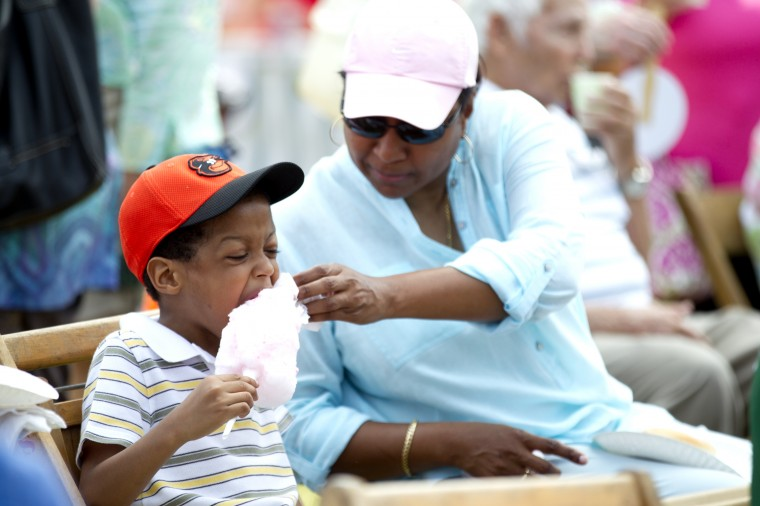 Shona Hudson, right, of Catonsville helps her son Shannon Ross, left, 7, while he eats some cotton candy during the 136th annual Clarksville Picnic at St. Louis Catholic Church in Clarksville, MD on Saturday, June 28, 2014. (Jen Rynda/BSMG)
