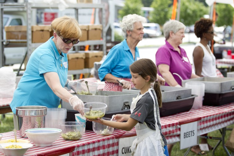 Volunteer Betsy Haney, left, of Glenwood hands some cucumbers to volunteer Anja Suhar, 8, of Clarksville to serve during the 136th annual Clarksville Picnic at St. Louis Catholic Church in Clarksville, MD on Saturday, June 28, 2014. (Jen Rynda/BSMG)