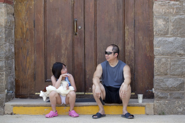 Jamie Tran, left, 9, of Gaithersburg and her father Joe Tran, right, cool off in the shade during the 136th annual Clarksville Picnic at St. Louis Catholic Church in Clarksville, MD on Saturday, June 28, 2014. (Jen Rynda/BSMG)