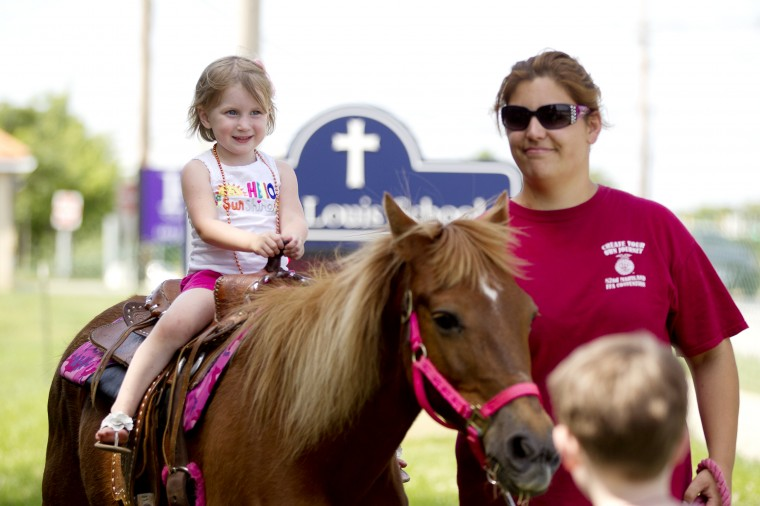 Anna Connolly, 4, of North Carolina rides a pony during the 136th annual Clarksville Picnic at St. Louis Catholic Church in Clarksville, MD on Saturday, June 28, 2014. Her family is visiting her gradparents who live in Columbia. (Jen Rynda/BSMG)