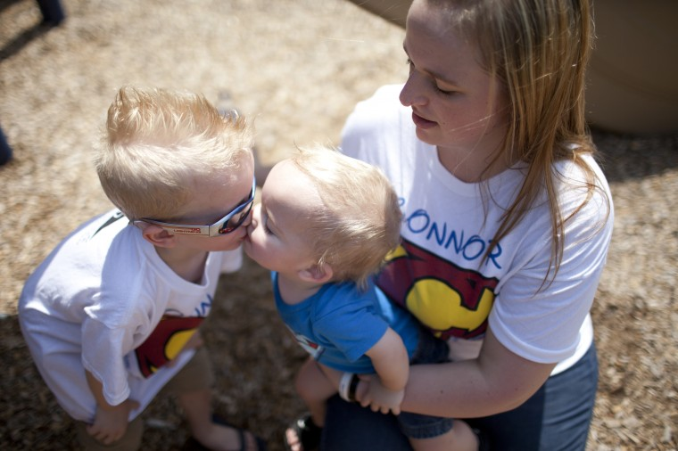 Connor Berry, 22 months, of Lansdowne gives a kiss to his older brother Camden Berry, 5, while at Hillcrest Park with their mother Caitie Berry in Lansdowne, MD on Thursday, July 3, 2014. (Jen Rynda/BSMG)