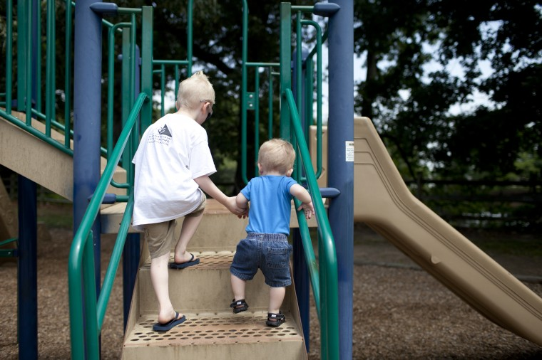Camden Berry, left, 5, of Lansdowne holds his little brother Connor Berry's, right, 22 months, hand while playing at Hillcrest Park with their mother Caitie Berry (not pictured) in Lansdowne, MD on Thursday, July 3, 2014. (Jen Rynda/BSMG)