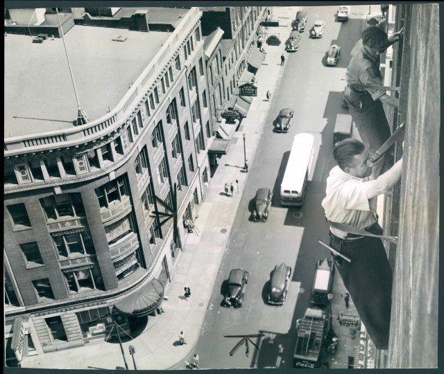 July 7, 1946: Robert Maxey and Stanley Medwid clean windows on the tenth floor of the Lexington Building. They are securred by their safety belts which are fastened to two little knobs on the sash frames. The squeegee, when not in use, is carried on the hip. (Photo by Albert D. Cochran)