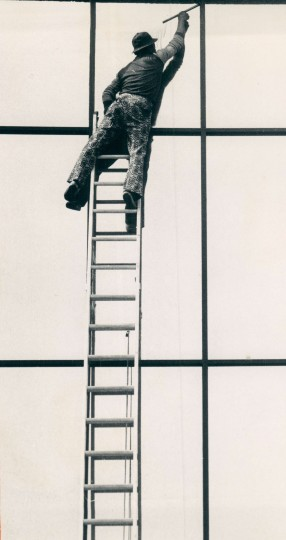 Feb. 27, 1976: A precarious perch for the window washer cleaning the exterior of the Dept. of transit and Traffic at Calvert and Bath. (Carl D. Harris - Sunpaper)