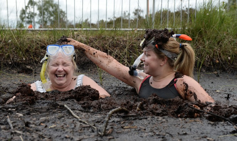 Two female entrants take a dip in the Bog Jacuzzi after takes part in the Irish Bog Snorkelling championship this afternoon at Peatlands Park on July 27, 2014 in Dungannon, Northern Ireland. The annual event sees male and female competitors swim the 60m length of the bog watched by scores of spectators and takes place on International Bog Day. (Charles McQuillan/Getty Images)