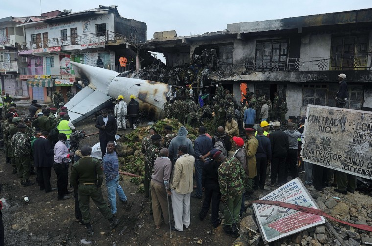 Rescuers and onlookers look at the wreckage of a cargo plane which crashed at a commercial building in a Nairobi suburb shortly after takeoff from the Kenyan capital's main airport, the busiest in east African. The Fokker 50 cargo airplane crashed with four crew just outside the airport as it took off to ferry khat to neighboring Somalia. (Tony Karumba/Getty Images)