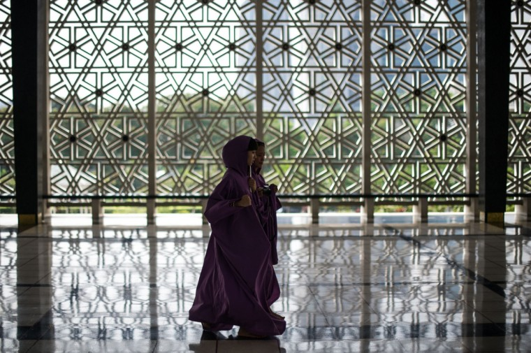 Non-Muslim tourists covered in robes walk inside a mosque during the holy fasting month of Ramadan in Kuala Lumpur. Islam's holy month of Ramadan is celebrated by Muslims worldwide marked by fasting, abstaining from foods, sex and smoking from dawn to dusk for soul cleansing and strengthening the spiritual bond between them and the Almighty. (Mohd Rasfan/Getty Images)