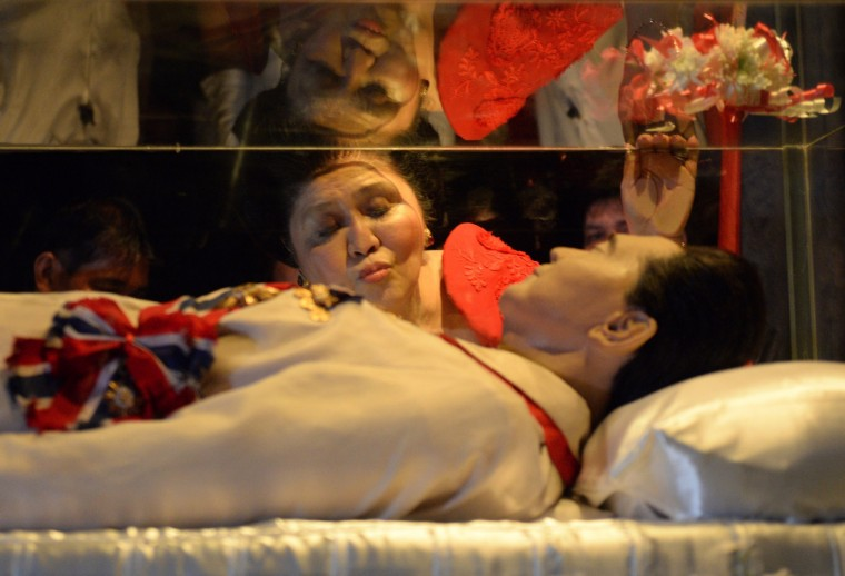 Former Philippine first lady and now congresswoman, Imelda Marcos, kisses the glass case of her late husband president Ferdinand Marcos during a visit to the mausoleum on her 85th birthday in Batac town, Ilocos norte, north of Manila. Marcos, a former first lady who was accused, but never convicted, of stealing state billions to support a profligate lifestyle during her late husband's 20-year rule, throws a party in the family's northern Philippines stronghold to celebrate her 85th birthday. (Ted Aljibe/Getty Images)