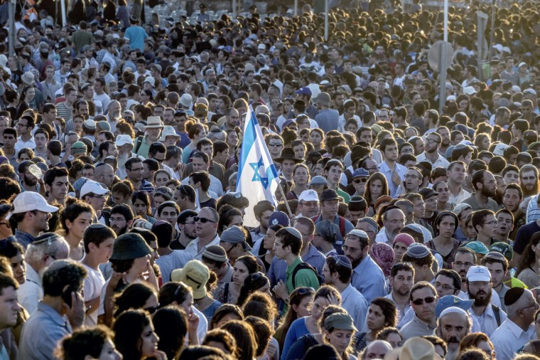 Tens of thousands Israelis attend the joint funeral of Gilad Shaer, 16, Naftali Frenkel, 16, and Eyal Ifrach, 19, in the central Israeli town of Modiin. The three had disappeared from a roadside in the southern West Bank on June 12, and on June 30 their bodies were found in a nearby field, with Israel blaming Hamas for their abduction and death and vowing to hunt down the killers. (Jack Guez/Getty Images)