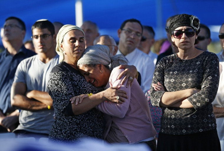 Bat-Galim Shaer (R) and Iris Ifrach (C), the mothers of two of the three Israeli teenagers killed in the West Bank mourn during the funeral of their sons in the cemetery of Modiin in central Israel. Israel paid an emotional farewell to Gilad Shaer and Naftali Frenkel, both 16, and 19-year-old Eyal Ifrach, while vowing to hunt down the Hamas militants it holds responsible for their kidnap and murder. (Baz Ratner/Getty Images)