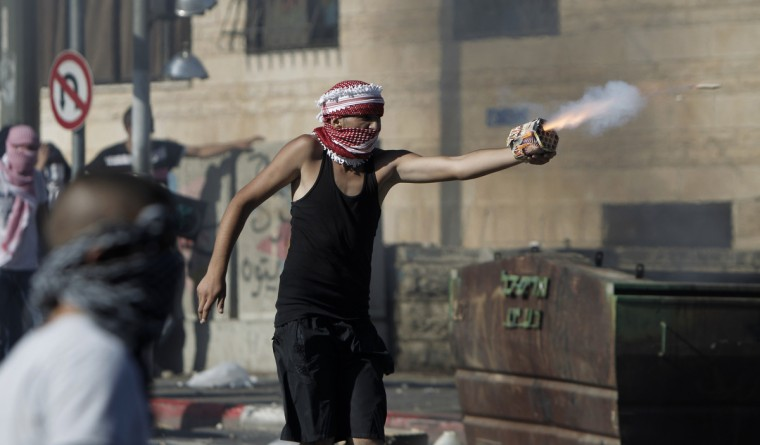 A Palestinian protestor directs fireworks toward Israeli police during clashes in Shuafat neighborhood in Israeli-annexed Arab East Jerusalem, on July 2, 2014, after a Palestinian teenager was kidnapped and killed in an apparent act of revenge for the murder by militants of three Israeli youths. (Ahmad Gharabli/Getty Images)