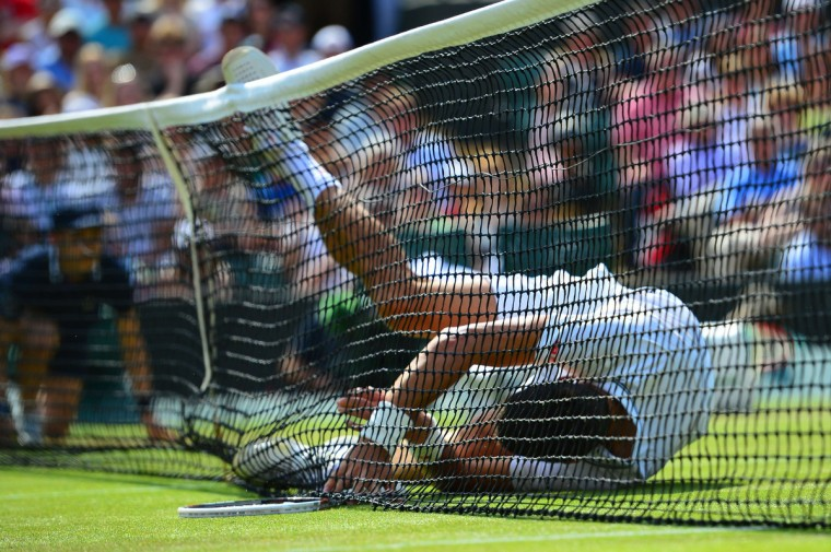 Serbia's Novak Djokovic falls into the net during his men's singles quarter-final match against Croatia's Marin Cilic on day nine of the 2014 Wimbledon Championships at The All England Tennis Club in Wimbledon, southwest London. (Carl Court/Reuters)