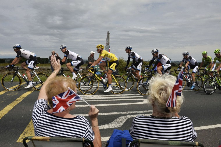 Supporters wave along the road as Germany's Marcel Kittel (C), wearing the overall leader's yellow jersey, rides past during the 201 km second stage of the 101th edition of the Tour de France cycling race on July 6, 2014 between York and Sheffield, northern England. (Jeff Pachoud/Getty Images)
