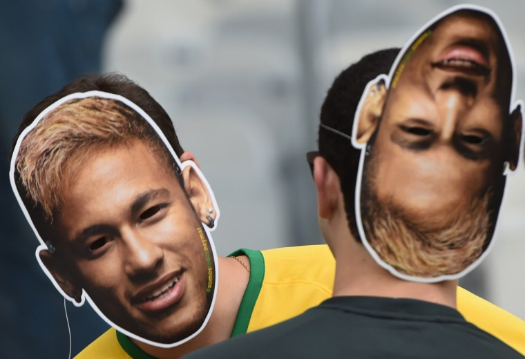 Brazilian fans wearing Neymar masks bearing the images of Brazil's forward Neymar, who is not playing due to an injury, cheer prior to the semi-final football match between Brazil and Germany at The Mineirao Stadium in Belo Horizonte during the 2014 FIFA World Cup on July 8, 2014. (Pedro Ugarte/Getty Images)