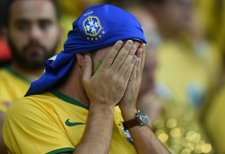 Brazilian fan react during the semi-final football match between Brazil and Germany at The Mineirao Stadium in Belo Horizonte during the 2014 FIFA World Cup on July 8, 2014. (Venderlei Almeida/Getty Images)