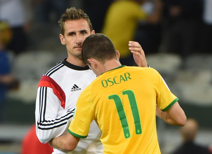 Germany's forward Miroslav Klose (L) conforts Brazil's midfielder Oscar after the semi-final football match between Brazil and Germany at The Mineirao Stadium in Belo Horizonte during the 2014 FIFA World Cup on July 8, 2014. (Pedro Ugarte/Getty Images)