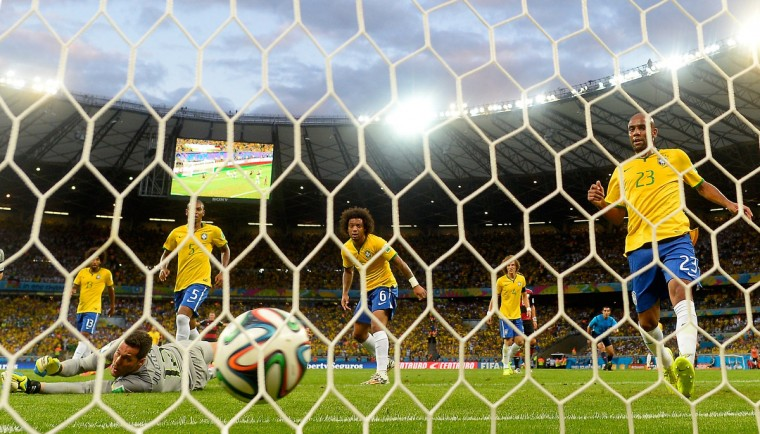 Brazil's goalkeeper Julio Cesar (L bottom) concedes a goal during the semi-final football match between Brazil and Germany at The Mineirao Stadium in Belo Horizonte during the 2014 FIFA World Cup on July 8, 2014. Germany won 7-1. (Adrian Dennis/Getty Images)
