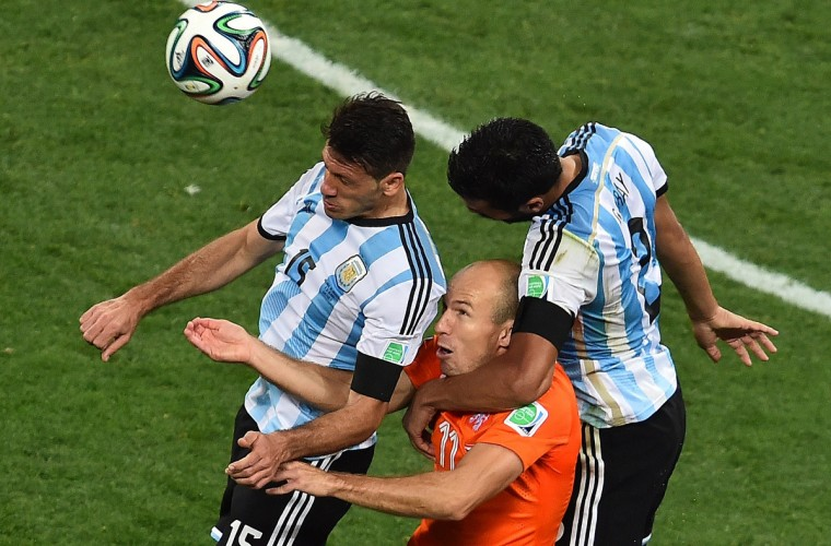 Netherlands' forward Arjen Robben heads the ball next to Argentina's defender Martin Demichelis (L) and Argentina's defender Ezequiel Garay during the semi-final football match between Netherlands and Argentina of the FIFA World Cup at The Corinthians Arena in Sao Paulo on July 9, 2014. (Gabriel Bouys/Getty Images)