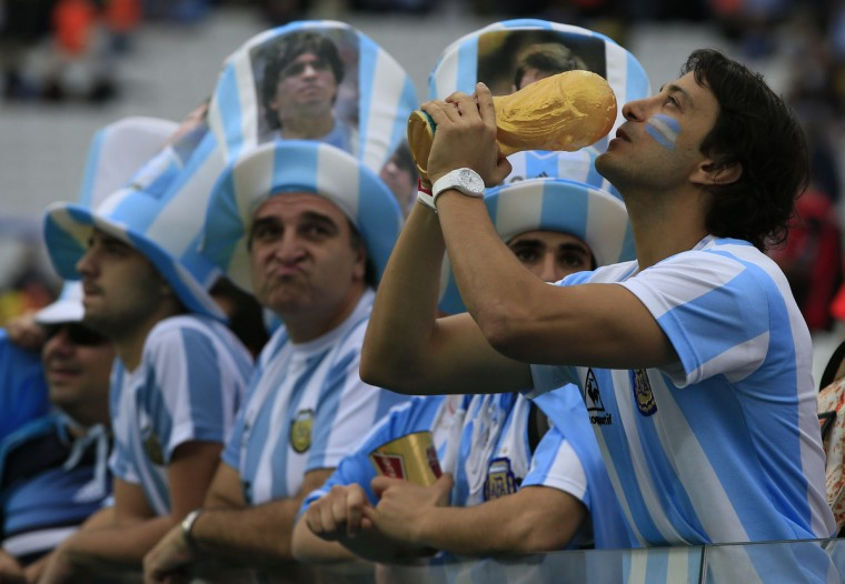 An Argentinian fan holds a replica of the world cup trophy before the semi-final football match between Netherlands and Argentina of the FIFA World Cup at The Corinthians Arena in Sao Paulo on July 9, 2014. (Adrian Dennis/Getty Images)