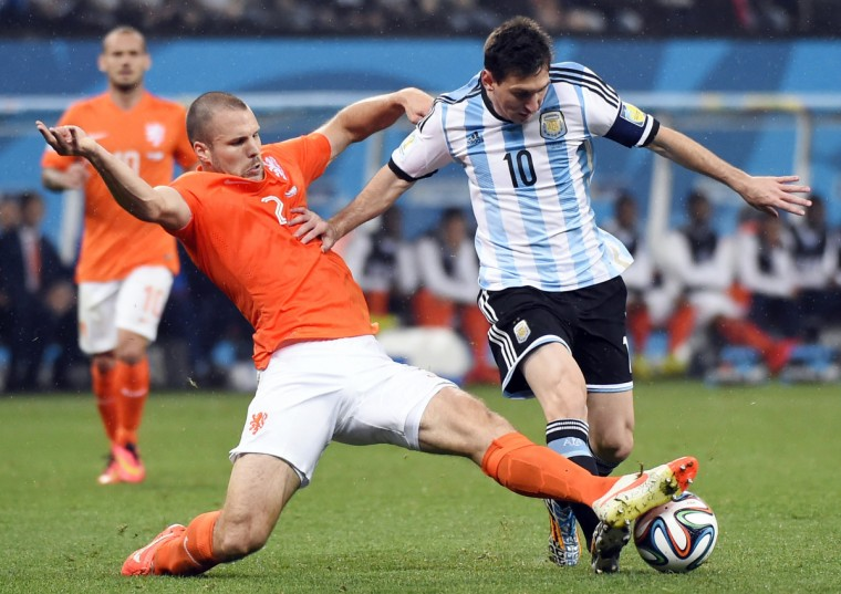 Netherlands' defender Ron Vlaar (L) and Argentina's forward and captain Lionel Messi vie for the ball during the semi-final football match between Netherlands and Argentina of the FIFA World Cup at The Corinthians Arena in Sao Paulo on July 9, 2014. (Fabrice Corrrini/Getty Images)
