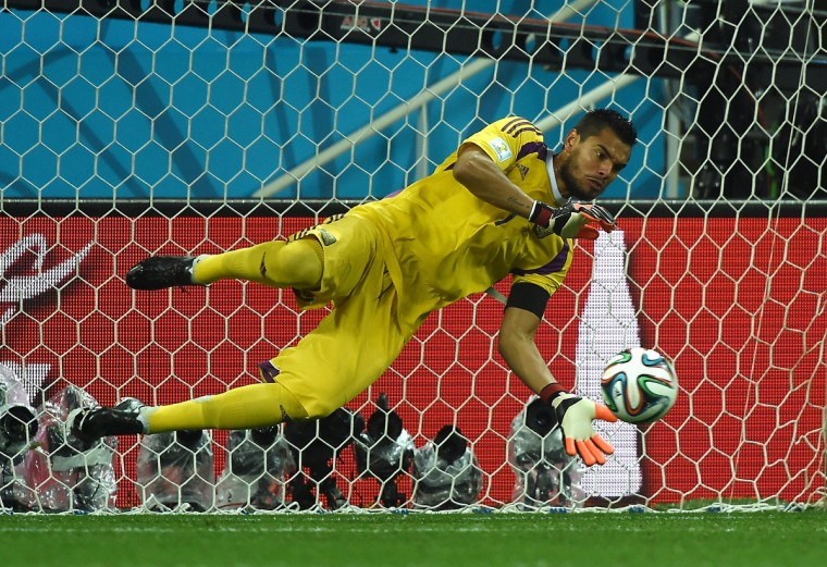 Argentina's goalkeeper Sergio Romero makes a save from Netherlands' defender Ron Vlaar during a penalty shoot out following extra-time in the semi-final football match between Netherlands and Argentina of the FIFA World Cup at The Corinthians Arena in Sao Paulo on July 9, 2014. (Pedro Ugarte/Getty Images)