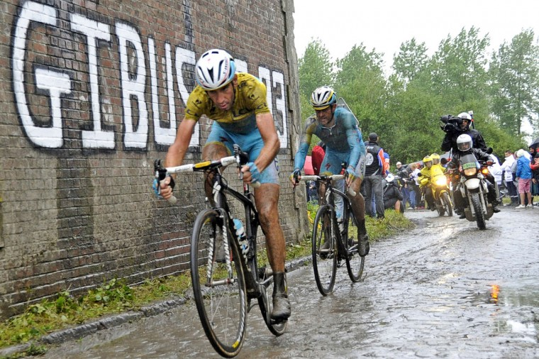 Italy's Vincenzo Nibali (L) wearing the overall leader's yellow jersey rides during the 152,5 km fifth stage of the 101st edition of the Tour de France cycling race on July 9, 2014 between Ypres, northwestern Belgium, and Arenberg Porte du Hainaut in Wallers northern France. (Francois Lo Presti/Getty Images)