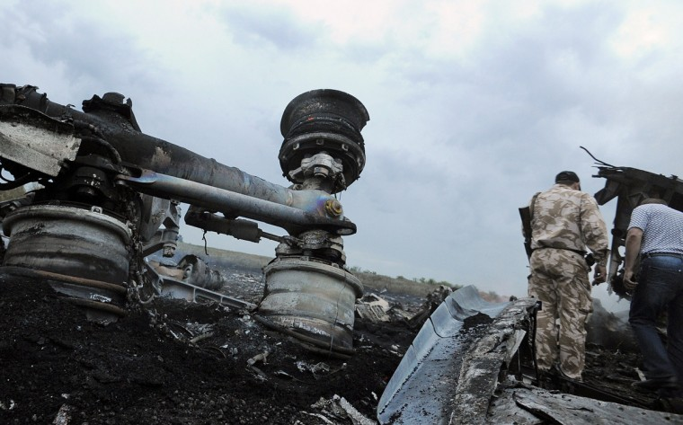 A man wearing military fatigues stands next to the wreckages of the Malaysian airliner carrying 295 people from Amsterdam to Kuala Lumpur after it crashed, near the town of Shaktarsk, in rebel-held east Ukraine, on July 17, 2014. Pro-Russian rebels fighting central Kiev authorities claimed on Thursday that the Malaysian airline that crashed in Ukraine had been shot down by a Ukrainian jet. (Dominique Faget/Getty Images)