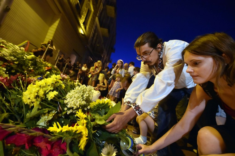 "People lay flowers in front of the Embassy of the Netherlands in Kiev on July 17, 2014, to commemorate passengers of Malaysian Airlines flight MH17 carrying 295 people from Amsterdam to Kuala Lumpur which crashed in eastern Ukraine. Ukrainian President Petro Poroshenko said on July 17 that the Malaysia Airlines jet that crashed over rebel-held eastern Ukraine may have been shot down."" Ukraine's government and pro-Russian insurgents traded blame for the disaster, with comments attributed to a rebel commander suggesting his men may have downed Malaysia Airlines flight MH17 by mistake, believing it was a Ukrainian army transport plane. (Sergei Supinsky/Getty Images)"