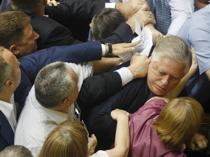 "Deputies of the All-Ukrainian Union ""Svoboda"" party attack the head of the Communist parliamentary faction Petro Symonenko (R) as they attempt to remove him from the hall during a Ukrainian parliament sitting in Kiev on July 23, 2014. Symonenko said in an interview with Russian media that the authorities in Ukraine had killed many thousands of Ukrainians in eastern Ukraine, where they are fighting pro-Russian rebels, and is profiting from the sale of their organs. (Anatoli Stepanov/AFP/Getty Images)"