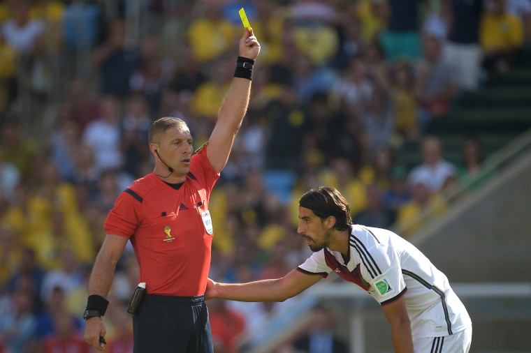 Referee Nestor Pitana shows Germany's Sami Khedira a yellow card during the World Cup quarterfinal match against France. (Alexandre Loureiro/Getty Images)