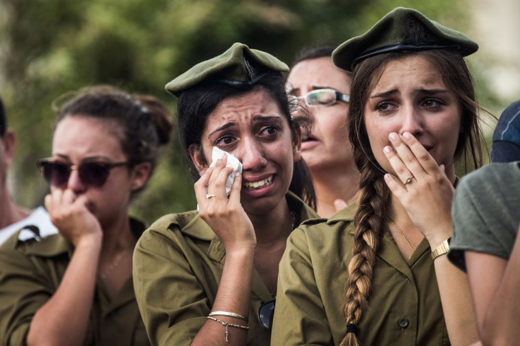 "Israeli soldiers weep at the grave of Israeli Sergeant Adar Barsano during his funeral on July 20, 2014 in Nahariya, Israel. Sergeant Barsano was killed along with another IDF soldier on the twelfth day of operation ""Protective Edge,"" when Hamas militants infiltrated Israel from a tunnel dug from Gaza and engaged Israeli soldiers. (Andrew Burton/Getty Images)"