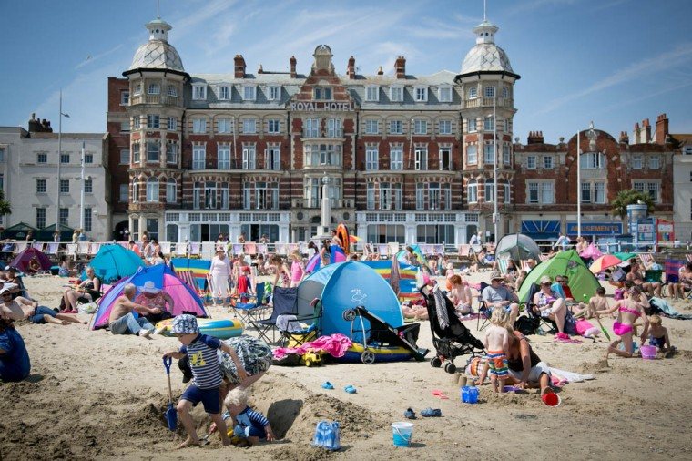 People gather on the beach as they enjoy the warm weather on the seafront on July 30, 2014 in Weymouth, England. Figures released by the Met Office show that this July is likely to go down as one of the warmest and sunniest on record. However the arrival of August will also see the return of more unsettled weather with the potential for heavy rain at the weekend. (Matt Cardy/Getty Images)