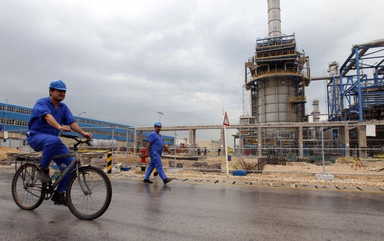... and a nuclear deal for Iran: A picture taken on January 27, 2011 shows an Iranian worker riding a bicycle through the Nouri Petrochemical facilities of the South Pars gas field in the southern Iranian port of Assaluyeh. Unblocking billions of dollars in funds to Iran under a landmark six-month nuclear deal with the West, that will take effect from January 20, 2014 will have a significant economic and psychological impact on the Islamic republic, experts said on January 13. (ATTA KENARE/AFP/Getty Images)