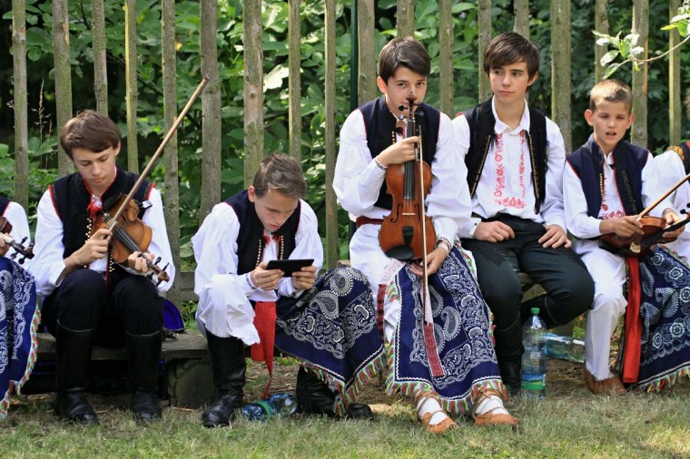 Young men sit on benches with instruments during the oldest folklore festival of Europe in Straznice, south Moravia, 80 km southeast from Brno, Czech Republic on June 29, 2014.  Leoš Janáček, a Czech composer who celebrated Moravian traditions in  much of his work was born 160 years ago today on July 3, 1854.     || CREDIT: RADEK MICA - AFP/GETTY IMAGES