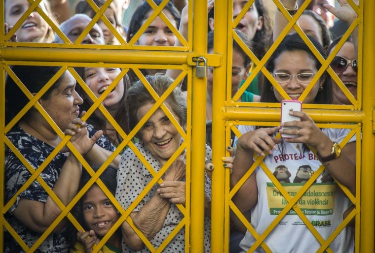 Brazilian football fans crowd outside the gate as their national team arrives for a training session at the President Vargas stadium on the eve of the FIFA World Cup 2014 quarter-final match between Brazil and Colombia in Fortaleza on July 3.   || CREDIT: ODD ANDERSEN - AFP/GETTY IMAGES