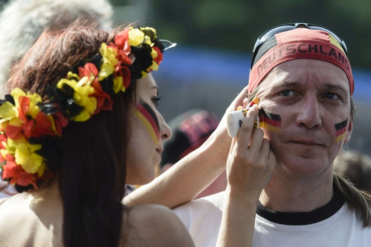 German fans in Berlin put on facepaint before watching a telecast of the World Cup quarterfinal match against France. (CLEMENS BILAN/AFP/Getty Images)