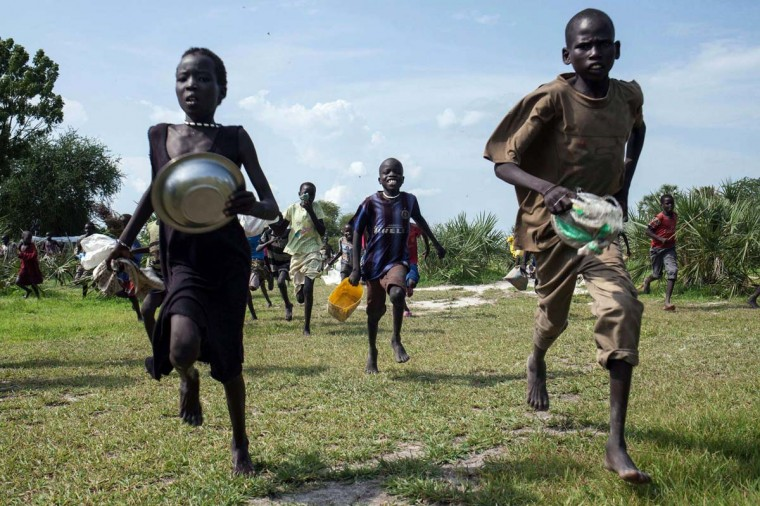 Children race into the drop zone to gather any food or seeds that were spilled during the air drop in Leer, South Sudan, on July 5, 2014. Over 40 tons of emergency food supplies and seed - enough for 1,100 families - were airdropped into Leer by the International Red Cross. These are the first air drops by the ICRC for nearly two decades, in an effort to reach hundreds of thousands of starving and malnourished people in South Sudan. (Nichole Sobecki/AFP/Getty Images)