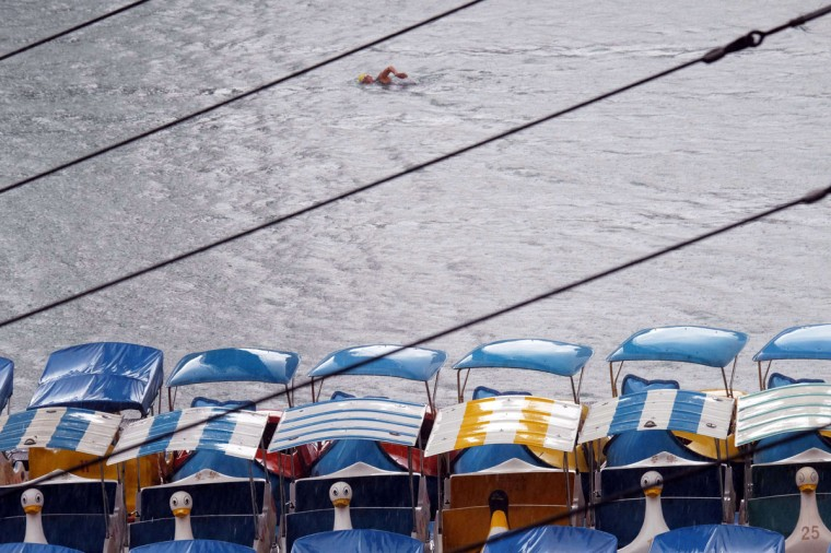 A man swims in the Hsintien river in the New Taipei City as typhoon Neoguri nears the eastern Taiwan on July 8, 2014. Japan was bracing for one of its worst storms in over a decade as typhoon Neoguri barreled towards the southern Okinawa island chain, with 55,000 people urged to evacuate as the weather agency issued its highest alert. (AFP/Getty Images/Sam Yeh)